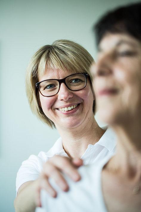 Therapeutin behandelt eine Patientin an der Schulter