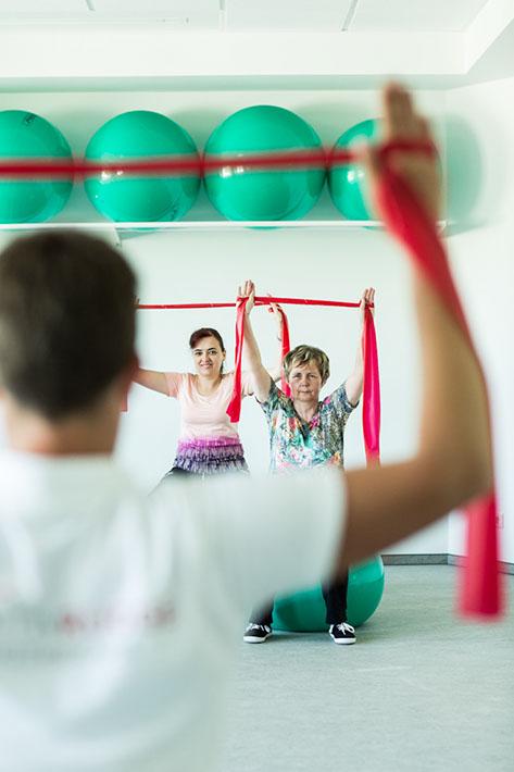 Kursteilnehmer trainieren mit Bändern
